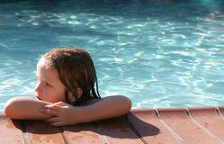 Young girl swimming. Young girl learning how to swim using a float Royalty Free Stock Image