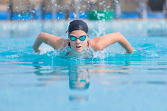 Young girl swimming butterfly stroke style. Young girl in goggles and cap swimming butterfly stroke style in the blue water pool Royalty Free Stock Photo