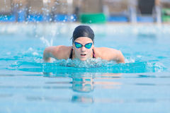 Young girl swimming butterfly stroke style. Young girl in goggles and cap swimming butterfly stroke style in the blue water pool Royalty Free Stock Photos