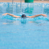 Young girl swimming butterfly stroke style. Young girl in goggles and cap swimming butterfly stroke style in the blue water pool Stock Photos