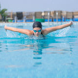 Young girl swimming butterfly stroke style Royalty Free Stock Photo