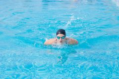 Young girl swimming butterfly stroke style. Young girl in goggles and cap swimming butterfly stroke style in the blue water pool Stock Photography