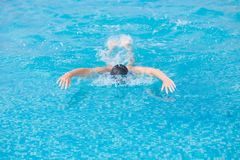 Young girl swimming butterfly stroke style. Young girl in goggles and cap swimming butterfly stroke style in the blue water pool Stock Photo