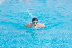 Young girl swimming butterfly stroke style. Young girl in goggles and cap swimming butterfly stroke style in the blue water pool Royalty Free Stock Image