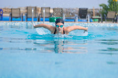 Young girl swimming butterfly stroke style. Young girl in goggles and cap swimming butterfly stroke style in the blue water pool Royalty Free Stock Photography