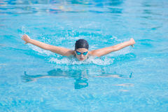 Young girl swimming butterfly stroke style. Young girl in goggles and cap swimming butterfly stroke style in the blue water pool Royalty Free Stock Images