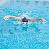 Young girl swimming butterfly stroke style. Young girl in goggles and cap swimming butterfly stroke style in the blue water pool Stock Image