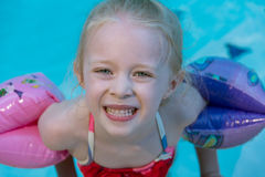 Young girl swimming. Little blond girl with inflated pink and blue water wings, swimming and looking up into the camera with a big smile Stock Photos