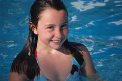 Young Girl swimming in pool. A happy smiling brown-eyed brown haired preteen girl swimming in a pool on a sunny day Royalty Free Stock Images