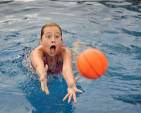 Young girl in swimming pool. Young brunette caucasian girl diving for orange ball in swimming pool Royalty Free Stock Photos
