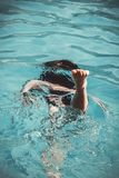 Young girl in the swimming pool diving under the water Royalty Free Stock Photography