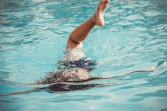 Young girl in the swimming pool diving under the water Royalty Free Stock Images