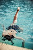 Young girl in the swimming pool diving under the water Stock Image