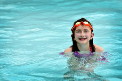 Young Girl Swimming in Pool with Orange Goggles Royalty Free Stock Photo