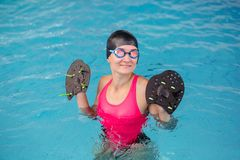 Young girl swimming in water pool with special equipment for hand. stock image