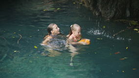 Young girl swimming in a waterfall. Young girls swimming in the beautiful mountain lake under waterfall, enjoying a swim.Two girls are swimming in a mountain stock video footage