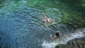 Young girl swimming in a waterfall. Young girls swimming in the beautiful mountain lake under waterfall, enjoying a swim.Two girls are swimming in a mountain stock footage