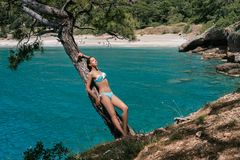 A young girl in a swimsuit is standing on a cliff above the sea. The model is enjoyed on a summer day. A woman is relaxing Stock Photography
