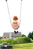 Young girl on swing. Rear view of red haired preschool girl on swing with house in background and white sky Royalty Free Stock Image