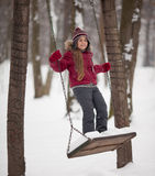 Young girl on a swing. A young girl playing on the swings at nice winter day Stock Images
