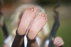 A young girl on a swing, close-up of feet Royalty Free Stock Photography
