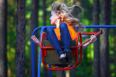 Young girl on a swing. Fitness and leisure. The fair-haired young lady during rest in city park Royalty Free Stock Photography