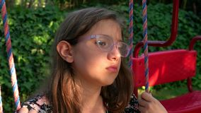 Young Girl is on Swing. In a playground video stock video footage