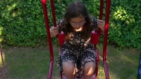 Young Girl is on Swing. In a playground video stock video
