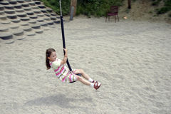 Young girl swinging 01. Young girl swinging on a playground Stock Photos