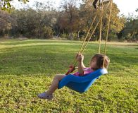 Young girl swinging Stock Images