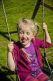 Young girl swinging at backyard Stock Photo