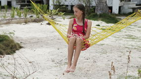Young girl swinging in a hammock. Young girl sitting and swinging in a hammock on the beach under palm trees stock video footage