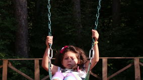 Young girl swinging in a playground stock video footage