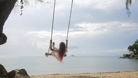 Young Girl Swinging on a Swing on the Beach. Tropical Island Peaceful Sea View HD Slowmotion. Koh Phangan, Thailand. stock video footage