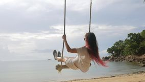 Young Girl Swinging on a Swing on the Beach. Tropical Island Peaceful Sea View HD Slowmotion. Koh Phangan, Thailand. stock footage