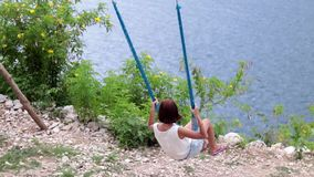 Young girl swinging on a swing in the mountains on a cliff above the ocean. Fantastic view, slow motion. Tropical island stock footage