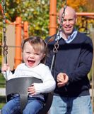 Young girl on swings being pushed by her father. Inpark setting Stock Images