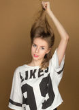 A young girl in a t-shirt playing with the hair Royalty Free Stock Image