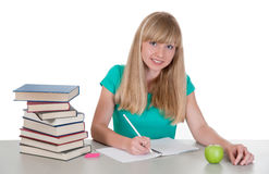 Young girl at the table with books Stock Images