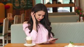 Young girl with tablet and coffee sitting in cafe. stock footage