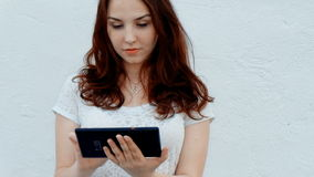 Young girl with a tablet PC outdoors. Concept of modern technology stock footage