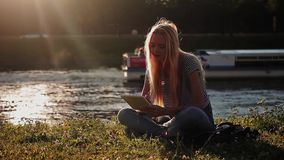 Young girl with tablet pc sitting on the green grass near the river stock video