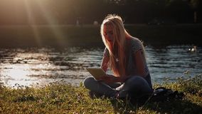Young girl with tablet pc sitting on the green grass near the river stock footage