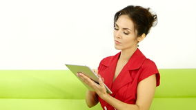 Young girl with tablet pc on the sofa stock footage