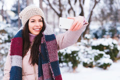 Young girl take a self portrait. Beautiful young long hair girl taking a self portrait with a smart phone on a winter time Royalty Free Stock Photo