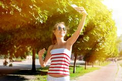 Young girl take selfie from hands with phone on street. Young girl take selfie from hands with phone on summer day Royalty Free Stock Images