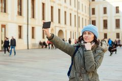 Young girl take selfie with phone on city street. Woman tourist smiling and making travel selfie. Happy girl enjoying vacation. royalty free stock photo
