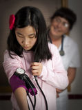 Young girl takes blood pressure Royalty Free Stock Image
