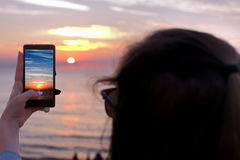 Young girl takes a picture of the sunset by smart phone Royalty Free Stock Images