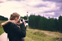 A young girl takes pictures of the forest.  Royalty Free Stock Photos